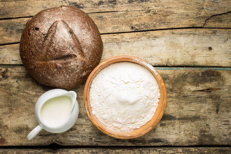 flour: Bakery ingredients with loaf of rye bread on weathered wood background.