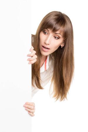 Amazed caucasian girl with empty billboard isolated on white background