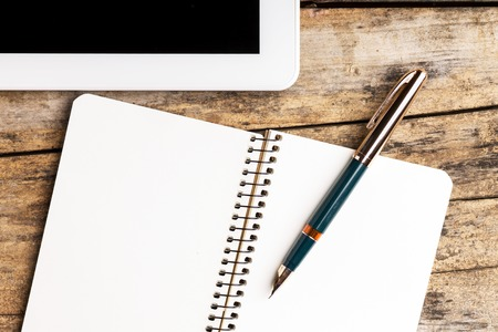 Workplace with digital tablet or pad and opened empty notebook with old golden fountain pen Stock Photo