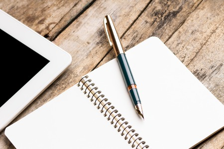Digital tablet with empty notebook and old fountain pen on rustic wooden table. Stock Photo