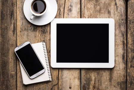 Digital pad with phone and notebook with cup of coffee. Stock Photo