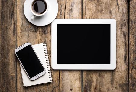 Digitale Unterlage mit Telefon und Notizbuch mit Tasse Kaffee.