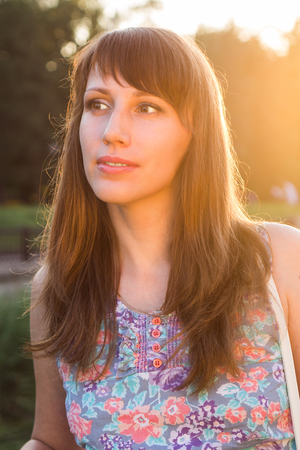 Pretty young woman glance away at summer day. Hipster caucasian girl dreaming at sunset beams