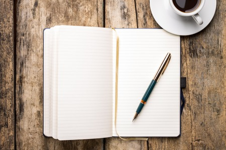 Notebook with elegant fountain pen and cup of espresso. Top view of writer's workplace