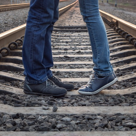 women kissing women: Young couple kissing at railways rails. Two people standing in love at summer day