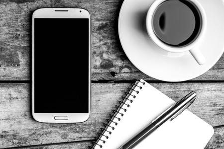 Kaffeepause Draufsicht Schwarz-Weiß-Bild. Smartphone mit Notebook, Füllfederhalter und Tasse Kaffee.