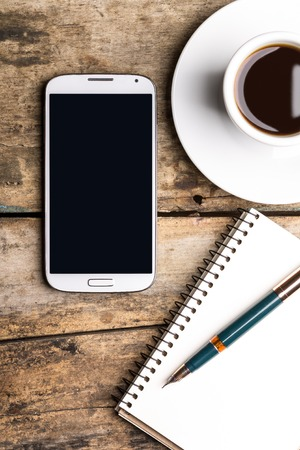 fountain pen: Smart phone with notebook and cup of strong coffee on wooden background. Cellphone with writing set with espresso