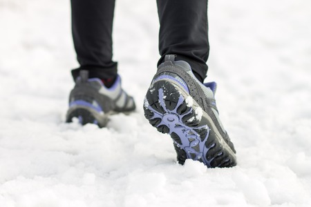Athlete woman jogging feet on snow at morning training. Sport background photo