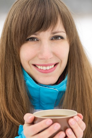 Happy smiling girl with cup of cappuccino at winter outdoor. Beauty caucasian woman holding hot tea photo