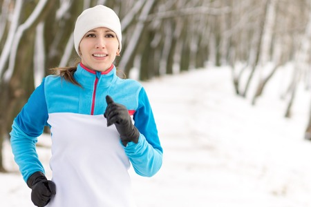 cold weather: Young smiling woman jogging at winter morning in park. Happy running caucasian girl image with copy space