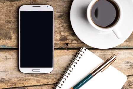phone: Smartphone with notebook and cup of strong coffee on wooden background. Cell phone with writing set with espresso