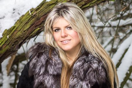 manteau de fourrure: Belle jeune femme blonde posant � la for�t d'hiver. Sourire fille caucasien portant un manteau de fourrure au bois neigeux