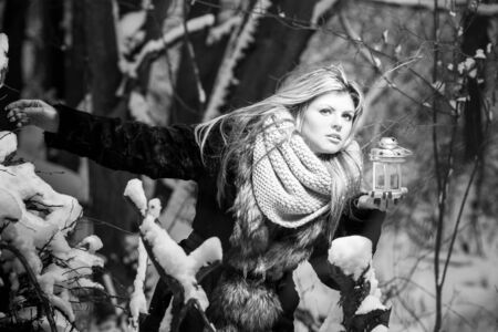stared: Scared young woman with candle in forest. Black and white image
