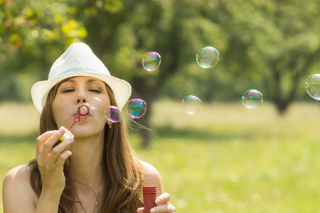 pretty: Young pretty woman have fun with soapbubbles in summer park. Caucasian hipster girl in hat flow out bubbles