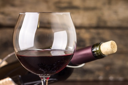 Red wine in wineglass against corked bottle on wood background 스톡 콘텐츠