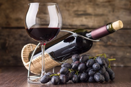 wine bottle: Winery background. Elegant wineglass with bottle of red wine and cluster of grape.