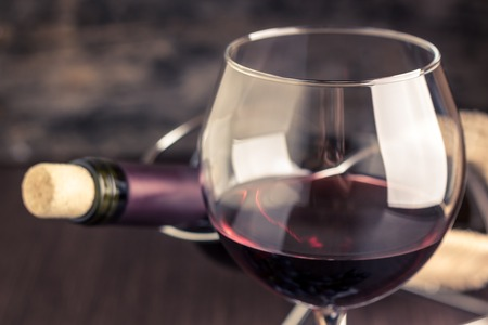 corked: Red wine in wineglass against corked bottle on wood background. Warm color toned image