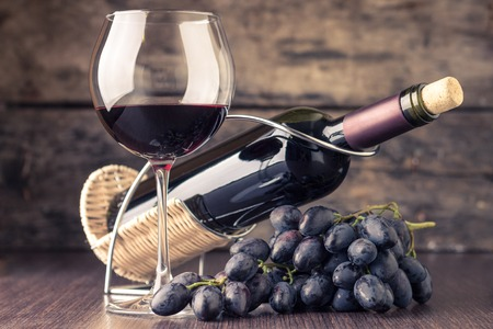 cabernet sauvignon: Winery background. Wineglass with bottle of red wine and cluster of grape on wooden table. Toned image Stock Photo