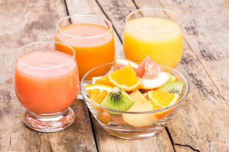 Gesundes Getränk Hintergrund. Frischer Fruchtsalat mit verschiedenen Saft im Glas auf Holztisch