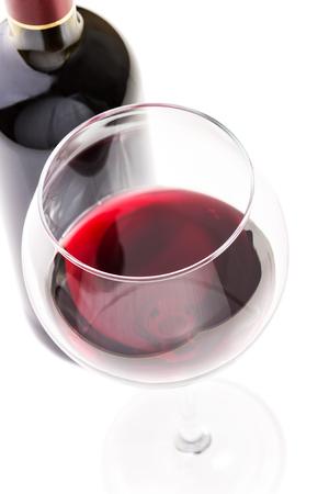 copa de vino: Vino rojo en vidrio con botella aislada en el fondo blanco. Vista superior Imagen de concentraci�n selectiva