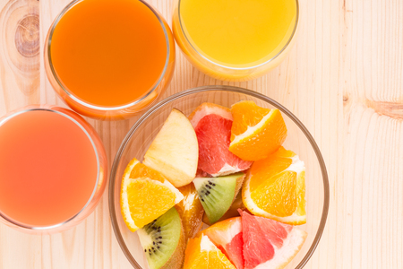 Fresh juices in three glasses with fruit salad. Vitamins background top view image photo