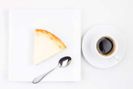 rebanada de pastel: Breakfast eating background. Cup of coffee with piece of cheesecake on plate. Cup of espresso with dessert on white table