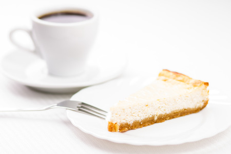 espesso: Piece of fresh baked cheesecake with cup of espesso coffee on white table