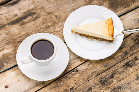 Cup of coffee with slice ofcheesecake on cake server. Breakfast eating background. 스톡 콘텐츠