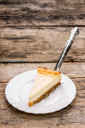 recipe background: Piece of New York style cheesecake with beauty cake server on wooden table. Dessert recipe background with copy space