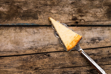 Slice of new york cheesecake on beauty cake server on old wooden table. Restaurant dessert menu background.