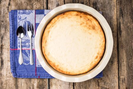 recipe background: Fresh baked cheesecake on wooden table. Dessert cooking recipe background. Top view image