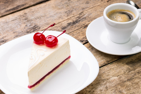 New York style cheesecake with cup of coffee on wood background. Piece of cake with cherry and espresso. photo