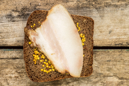 mustard seed: Rural meal time background. Top view image of bacon sandwich with mustard seed