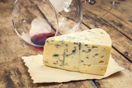 warm color: Warm color toned image of cheese and wine background. Blue cheese with overturned wineglass.