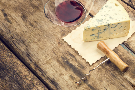 Blauschimmelkäse auf Weinlesepapierblatt mit umgestürzten Glas Wein und Korkenzieher. Warm getönten Farbe mit Exemplar.