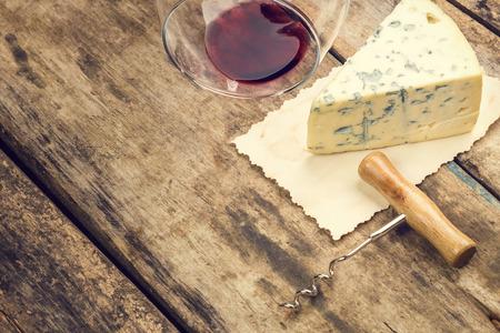 Blauwe kaas op vintage papier blad met ten val gebracht glas wijn en een kurkentrekker. Warme kleuren getinte afbeelding met copyspace.