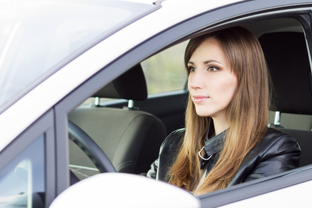 female driver: Beauty young business woman in a white car. Smiling caucasian girl in leather jacket drive holding wheel