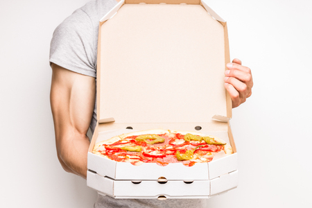 caja de pizza: El hombre joven sostiene cajas de pizza. caja abierta con la pizza en las manos