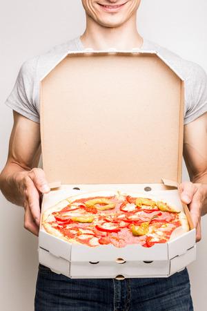 Junger Mann bietet Pizza Diabola. Pizza Lieferung Kurier hält zwei Boxen in die Hände