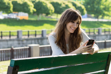Young beauty woman have fun with using smartphone sitting on bench. Happy caucasian girl texting with phone in city park