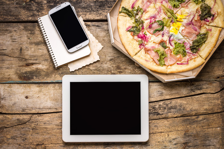 Mock up freelancer workplace. Tablet PC, cell phone and pizza. Top view image. Fast pizza delivery
