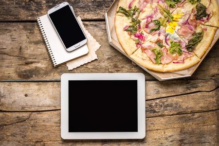 Mock-up freier Mitarbeiter am Arbeitsplatz. Tablet PC, Handy und Pizza. Draufsichtbild. Schnelle Pizzalieferung