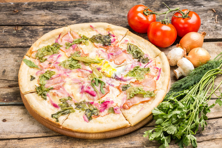gourmet pizza: Gourmet pizza with ingredients around. Sliced pizza with onion, tomato and herbs on wooden table. Stock Photo