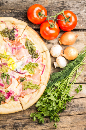 Pizza ingredients recipe and menu background. Top view image of half of pizza with vegetables around. Stock Photo