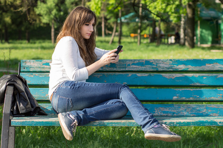 Pretty young woman using smartphone sitting on bench in park at summer day. Resting girl on the bench
