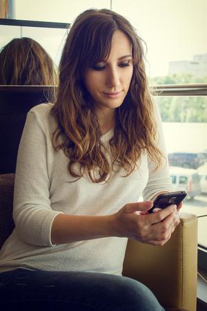 Jonge vrolijke vrouw zit in restaurant met behulp van smartphone. Warme kleuren getinte afbeelding van mooie meisje met gadget in cafe Stockfoto