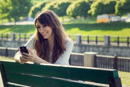 Jonge mooie vrouw chatten met behulp van de telefoon. Glimlachend Kaukasisch meisje plezier hebben met behulp van smartphone in park Stockfoto