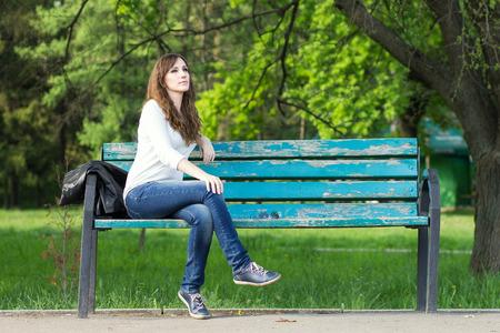 Mladá krásná žena, sedící na lavičce v parku. Hezká dívka na venku na letní den. Příroda životní prostředí na pozadí.