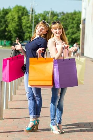 chicas divirtiendose: Ni�as gemelas j�venes que se divierten con la risa con sus bolsas de compras. Mujeres bastante cauc�sica de pie cerca de estacionamiento de espera para un taxi