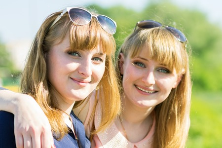 Pretty twins girls having fun at outdoor summer park. Young smiling women with glasses looking in camera Stock Photo